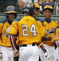 Chicago's Trey Hondras (24) is greeted by teammates after hitting a two-run home run off Las Vegas' Brennan Holligan in the first inning of a United States Championship game at the Little League World Series tournament in South Williamsport, Pa., Saturday, Aug. 23, 2014. (AP Photo/Gene J. Puskar