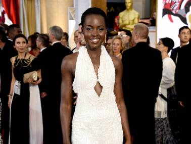 In this Sunday, Feb. 22, 2015 photo, actress Lupita Nyong'o arrives at the Oscars wearing a dress made of pearls at the Dolby Theater in Los Angeles.