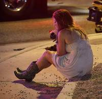 Sheri Sletten sits on a curb at the scene of a shooting outside of a music festival along the Las Vegas Strip, Monday, Oct. 2, 2017, in Las Vegas. Multiple victims were being transported to hospitals after a shooting late Sunday at a music festival on the Las Vegas Strip.