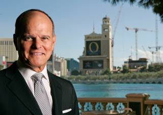 Terry Lanni, former chairman of the board and CEO of then-MGM Mirage, poses at the Bellagio in September 2007. Construction cranes from the CityCenter project can be seen at right.