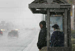 Bus riders wait at a shelter during a snowstorm near ...
