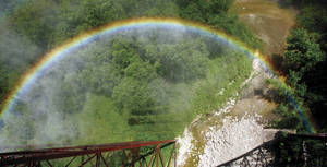 As a train engine releases steam, a rainbow is formed ...
