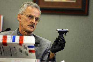 Metro Police Detective Peter Calos holds a .38 caliber handgun owned by Erik Scott during a coroner's inquest for Erik Scott at the Regional Justice Center Monday, September 27, 2010. The gun was said to be found in Scott's pocket by medical workers in the ambulance.