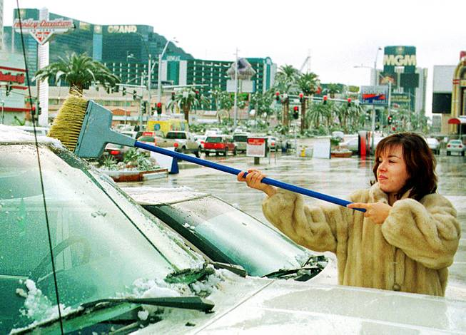 Madlen Nazrian, a UNLV student, sweeps snow off her boyfriend's truck after a rare snowstorm over the Las Vegas Strip Sunday morning, December 6, 1998. Nazrian, originally from Bulgaria, said she is used to winter weather since it snows a lot in her home country.