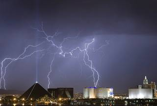 Lightning strikes behind the Luxor, left, and Excalibur hotel-casinos as a thunderstorm passes through Las Vegas early in the morning of September 11, 2011.