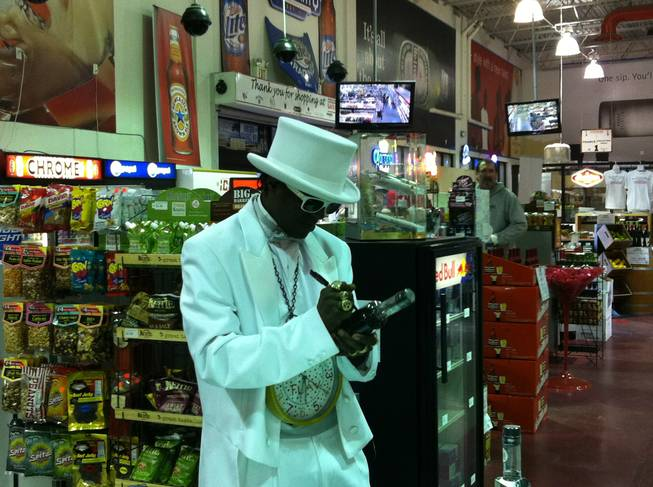 Rapper and reality television star Flavor Flav signs a bottle of his LeFLAV vodka at Lee's Discount Liquor on Lake Mead Boulevard on Dec. 23, 2011.