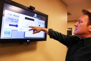 Frank Yoder, the president of WinTech, demonstrates ALICE, an automated reception system developed by the Las Vegas-based  software company, inside the reception area of the WinTech offices on Thursday, March 29, 2012.