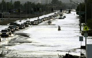 Pedestrians wade across Craig Road near U.S. 95  after a powerful thunderstorm dumped three inches of rain in about 90 minutes in the northwest section of the city Wednesday, August 19, 2003. The torrential downpour caused flash flooding that swamped neighborhoods and trapped people in their cars.