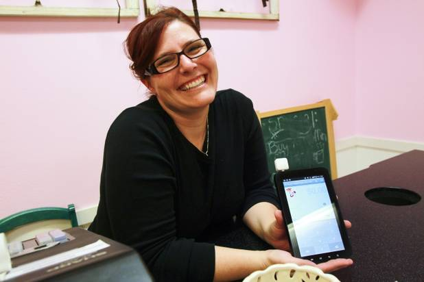 Angela Wallace shows the Square app she uses to process debit and credit card payments at her Lil' Brown Sugar's Cupcake Cafe in Henderson.