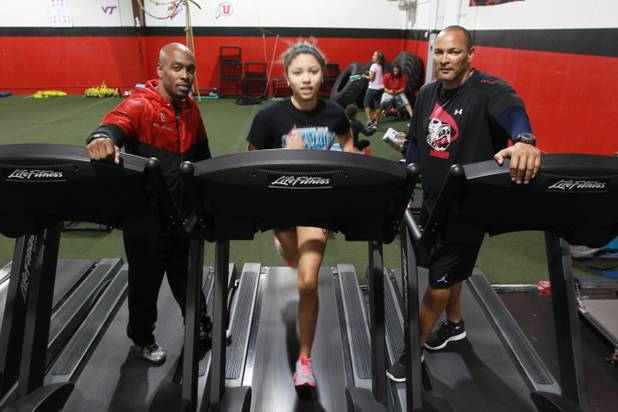 Phase 1 Sports owners Mike Waters, left, and Mel Spicer stand on either side as Silvestri Middle School student Mariah Morris works out on a treadmill. Phase 1 helps local athletes go to college and receive scholarships.