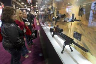 Show attendees look over a display of weapons at the Leupold Tactical Optics booth during the annual SHOT (Shooting, Hunting, Outdoor Trade) Show in the Sands Expo Center, Jan. 15, 2013.