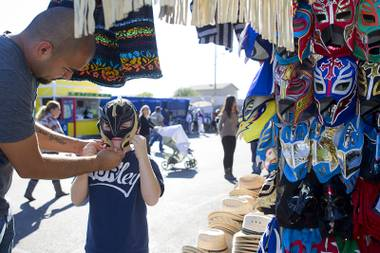 Anthony Alvarez, 9,  tries on a Mexican luchador (wrestling) mask with his father Miguel at the Broadacres Marketplace & Events Center Sunday Nov. 3, 2013.