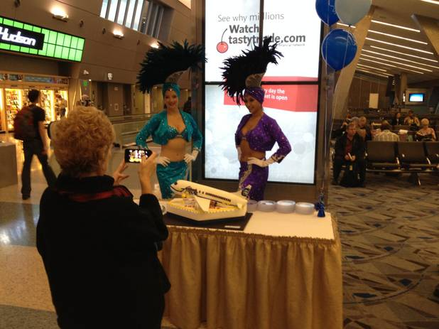 Marilyn Romano, regional vice president of Alaska for Alaska Airlines, takes a cellphone photo of a cake celebrating the inaugural flight from Anchorage, Alaska, to Las Vegas, at a Terminal 3 gate at McCarran International Airport on Dec. 19, 2013.