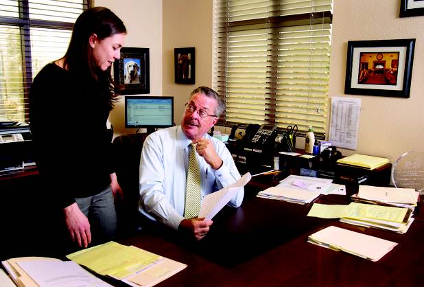 Attorney Al Marquis goes over documents with fellow attorney Kristin Gifford in the law offices of Marquis Aurbach Coffing.