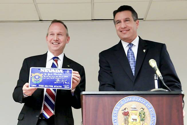 A screenshot of Nevada Gov. Brian Sandoval presenting Delaware Gov. Jack Markell with a Nevada sesquicentennial license plate as the two sign an agreement to pool their online poker venues in Wilmington, Del. Tuesday morning Feb. 25, 2014.