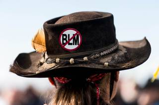 A protester, wearing an anti-Bureau of Land Management sign on his hat, listens to San Juan County Commissioner Phil Lyman at Centennial Park in Blanding, Utah on Saturday, May 10, 2014. Lyman organized an ATV protest ride into Recapture Canyon to show that the federal agency isn't the