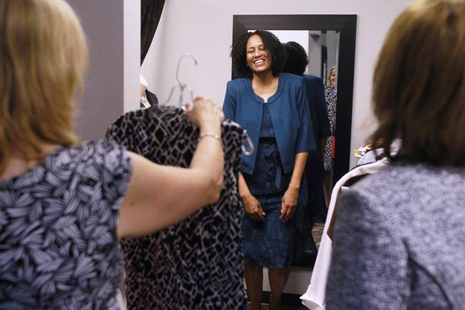 Sonji McTear smiles as Theresa Anderson, left, and Kelly Rissler find clothes for her to try on at Dress for Success Saturday, May 31, 2014.