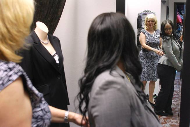 Theresa Anderson helps Mercedes Matlock check the fit of a jacket at Dress for Success Saturday, May 31, 2014.