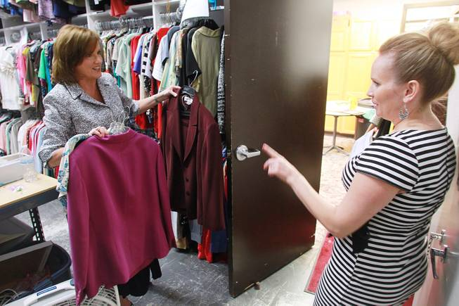 Volunteer Brenda Taylor, right, talks with manager Kelly Rissler as she picks out clothing for a client at Dress for Success Saturday, May 31, 2014.