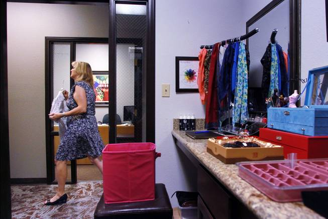 Theresa Anderson carries blouses to the dressing room for Sonji McTear to try at Dress for Success Saturday, May 31, 2014.