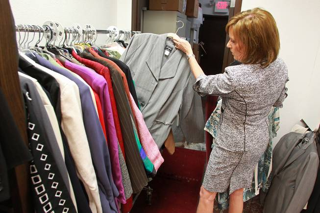Manager Kelly Rissler looks through clothing for a client to try on at Dress for Success Saturday, May 31, 2014.
