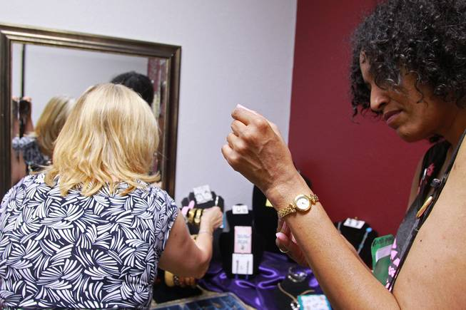 Sonji McTear tries on a watch as Theresa Anderson looks through other possible jewelry options at Dress for Success Saturday, May 31, 2014.