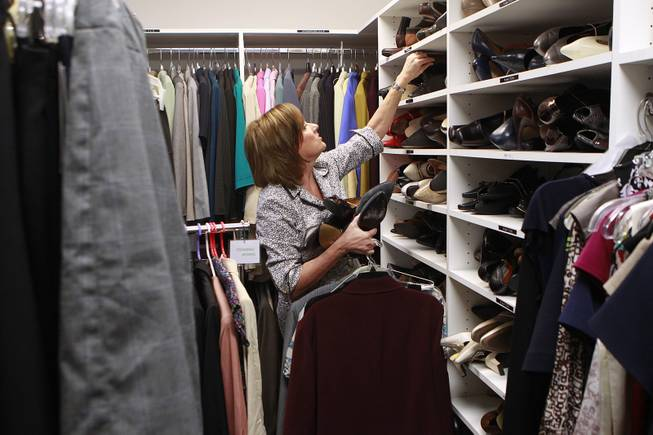 Manager Kelly Rissler looks through shoes for a client to try on at Dress for Success Saturday, May 31, 2014.
