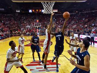 UNR guard Marqueze Coleman (1) gets off a shot just inside of UNLV forward Christian Wood (5) and others during their game at the Thomas & Mack Center on Wednesday, January 7, 2015.