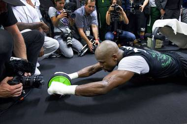 WBC/WBA welterweight champion Floyd Mayweather Jr., center, works on his abdominal muscles at the Mayweather Boxing Club Tuesday, April 14, 2015. Mayweather will face WBO welterweight champion Manny Pacquiao of the Philippines in a unification bout at the MGM Grand Garden Arena on May 2. .