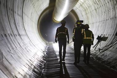 Claudio Cimiotti, left, senior tunnel engineer, walks with a news crew during a tour of the third intake tunnel under Lake Mead Monday, June 1, 2015.