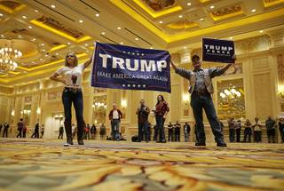 Sherry, left, and Tony Parsons hold up a sign before a rally with Republican presidential candidate Donald Trump, Sunday, Oct. 30, 2016, in Las Vegas.