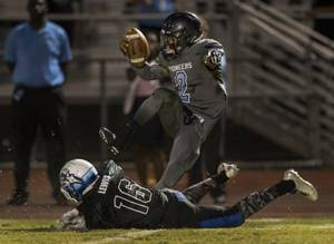 Canyon Springs QB Diamante Burton (2) evades another tackle by ...