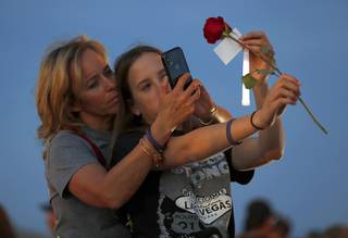 Kenzy Smith, 14, holds a rose for her mother Mynda Smith to photograph during a vigil, marking the six-month anniversary of the Oct. 1 mass shooting, near the Las Vegas Festival Grounds Sunday, April 1, 2018. Mynda's sister Neysa Tonks was one of the 58 victims of the shooting.