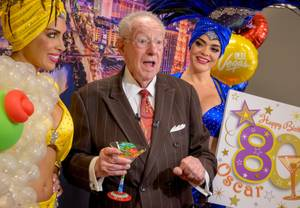 Las Vegas Convention and Visitors Authority (LVCVA) Host Committee Chairman Oscar B. Goodman, center, flanked by Showgirls Jennifer Johnson, left, and Porsha Revesz is interviewed following an 80th birthday celebration surprise during the regular meeting of the LVCVA Board of Directors at the Las Vegas Convention center Board Room on Tuesday, July 9, 2019. Goodman is the former three-term Mayor of the City of Las Vegas and has worked for the LVCVA  for the past eight years.