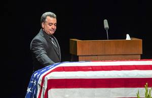 Long-time friend Dennis Flynn touches the casket during a memorial service for former Metro Police Capt. Larry Burns Jr. at the Smith Center Thursday, July 18, 2019. Flynn is a former Metro Police lieutenant.