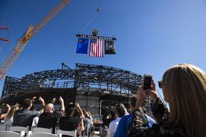 Attendees watch as the final iron beam is lowered during ...