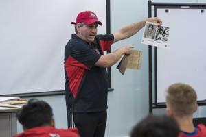 1969 Valley high state champion Jeff Eskin holds up a photo of former NFL player and Bishop Gorman graduate David Humm, as he speaks to the school's football team Wednesday, Sept. 4, 2019. WADE VANDERVORT