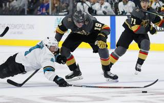 San Jose Sharks defenseman Brenden Dillon dives to knock the puck away from Vegas Golden Knights right wing Reilly Smith (19) during the second period of an NHL preseason hockey game Sunday, Sept. 29, 2019, in Las Vegas.