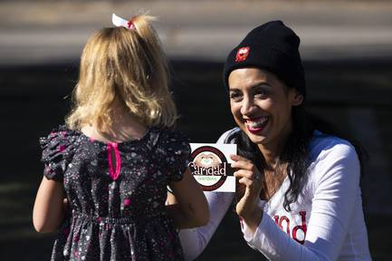 Caridad founder Meredith Spriggs gives Hennley Marting, 6, a sticker during the opening ceremony for the Caridad Gardens at Bunkhouse Saloon in  downtown Las Vegas, Monday, Nov. 11, 2019.