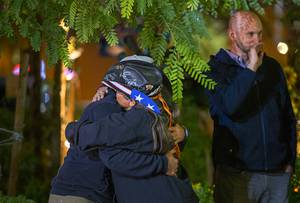 Sue Ann Cornwell, center, a survivor of the Oct. 1 mass shooting, gets a hug from Dylan Culwell during a Tree of Life lighting ceremony at the Las Vegas Community Healing Garden Tuesday, Nov. 26, 2019. Aaron Leifheit stands by  at right. This year's ceremony was dedicated to Kim Gervais. Gervais was injured in the Oct.1 mass shooting and passed away Nov. 1 of this year.