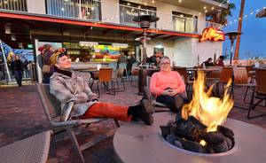 Heidi Rider, left, and Vicky Blake warm up by the fire pit at the La Monja Cantina during the Fergusons Downtown grand opening at 1028 Fremont St. in Las Vegas on Friday, Dec. 13, 2019. Fergusons Downtown is a former hotel converted to a retail, restaurant and entertainment space.