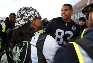 Tight end Darren Waller talks with a construction worker in Raiders garb during a news conference to officially rename the Oakland Raiders to the Las Vegas Raiders, in front of Allegiant Stadium, Wednesday, Jan. 22, 2020.