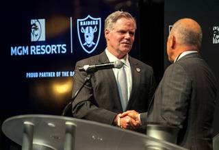 Jim Murren, left, chairman and CEO of MGM Resorts International,shakes hands with Marc Badain, president of the Las Vegas Raiders, during a news conference at Mandalay Bay Thursday, Jan. 23, 2020. MGM Resorts International announced a founding partnership with the Las Vegas Raiders.