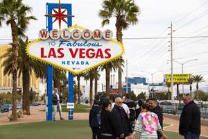 Tourists wait to get their photo taken at the Las Vegas Sign on the first day of the covid-19 quarantine, Wednesday, March 18, 2020.