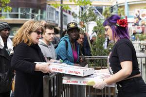 Alysia Bosnos, of Evel Pie, runs pizzas out to waiting locals as they give away free pizzas to anyone in need until their supply runs out, Wed. March 18, 2020. The announcement came after Governor Sisolak ordered a mandatory closure of all nonessential businesses the day prior.