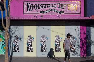 Artist Recycled Propaganda finishes a mural on a boarded up exterior of the Koolsville Tattoo and Body Piercing shop on Main Street, downtown, Tuesday, March 24, 2020.