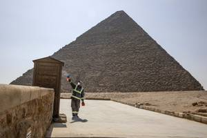 Municipal workers sanitize the areas surrounding the Giza pyramids complex ...