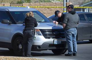 A crime scene analyst and Metro Police investigators confer near the scene of an apparent double murder and suicide in a residential area near Nellis and Lamb boulevards Friday, March 28, 2020. A man killed his two teenage sons before killing himself on Friday night, according to reports.