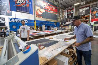Sean Southam and owner James Swanson look over a protective polycarbonate barrier at Screaming Images Thursday, May 7, 2020. The barriers have a variety of applications in gaming, business and office space.