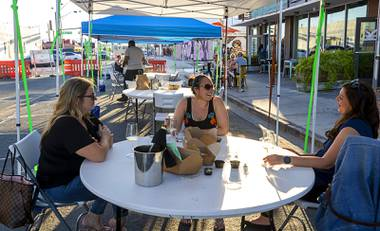 The City has closed off two streets to traffic to create a pair of urban dining areas, complete with socially distant tables, chairs, shade and portable trees.